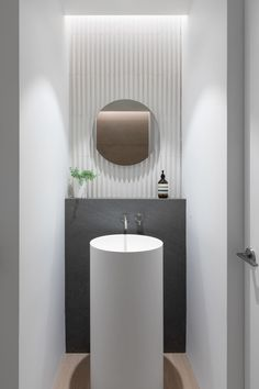 This modern powder room has a pedestal sink and faucet, a Basalt ledge, and Mutina tile on the wall. Enlisted by boutique builder Moosehead Contracting, Falken Reynolds Interiors and Randy Bens Architect designed a modern family home in Vancouver, Canada. Powder Room Decor, Powder Room Design, Modern Bathroom, Small Bathroom, Bathroom Interior, Bathroom Beach, White Bathrooms, Luxury Bathrooms, Industrial Bathroom