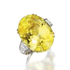 YELLOW SAPPHIRE AND DIAMOND RING The oval yellow sapphire weighing 36.21 carats, flanked by 2 trapeze-cut and 2 bullet-cut diamonds weighing approximately 1.40 carats, mounted in platinum and 18 karat gold