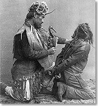 Chaman tlingit ligotant une sorcière, Hochet  tribu Huna. Sitka, Alaska Les sorcières étaient perçues comme des personnes qui cherchaient à causer du tort à leurs voisins par des moyens mystérieux. Elles ne faisaient pas de jeûne ni de purification, elles n'avaient pas non plus de contact avec des esprits adjoints, comme le font les chamans. Ce dernier cherchait à convaincre le malade de la supériorité de son esprit sur celui de la sorcière. Ainsi, il pouvait annuler le sort qu'elle aurait…