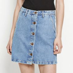 Penny Denim Mini Skirt: This a-line jean skirt by Samsoe & Samsoe has been cut from cotton denim fabric for a super soft and comfortable fit. The indigo blue wash has been aged giving a vintage finish which will look fab paired with almost anything. A staple transitional piece which will be a constant go to all year round. Front button fastening -A-line fit -Side Pockets -Belt holes -Vintage look -Mini length