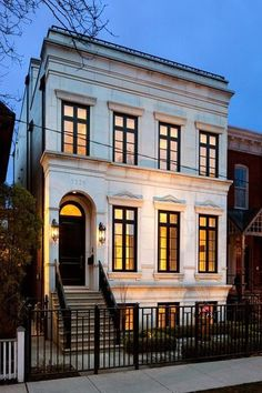 Neoclassical row house with limestone exterior accented with black framed windows