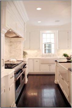 white kitchen, dark floors.