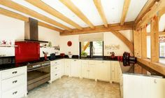Kitchen with exposed oak frame by Carpenter Oak Ltd