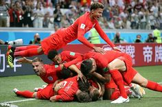 England players bury goalscorer Harry Kane to celebrate their opening goal against Tunisia.