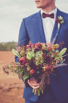 Groom wearing blue suite and burgundy bow tie with wild boho bouquet for desert wedding | Renee Lee