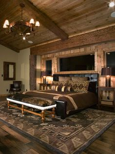 A combination of plank-styled ceiling and walls, exposed beams and wooden flooring add texture and bursts of warmth for this rustic master bedroom. Photo by High Camp Home