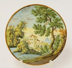 A Castelli maiolica Plate, c.1730, typically painted with a building with tall tower below towering rocks, a tree to one side, 17.5cm