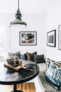 I love the table and light fixture. The pillows are a nice element and I like how they are all different but I don't think they need quite as many. The black framed art adds more contrast.