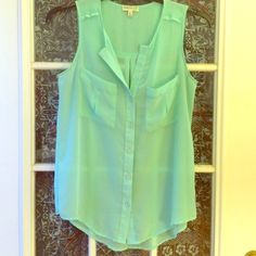 Sheer mint sleeveless blouse Sheer sleeveless mint sleeveless blouse. Button up with two pockets on front of blouse. Tops Blouses