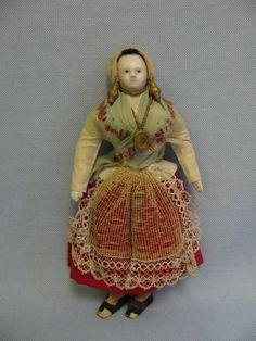eBay Image Hosting at www.auctiva.com~~... as a lady of Picardie, Amiens, France, she has a pouffed organdy bonnet, challis shawl wrapped over blouse with peplum and her considerable bosom. A gauze & lace apron covers her red wool skirt and two petticoats: striped denim and plain cotton, with cotton knit socks and original paper shoes.       Papier-mache head; kid leather body with wire inside for posing (not recommended due to age).  Ca. 1850
