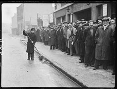 A photograph of a queue of unemployed men in London, taken in December 1938 by Saidman for the Daily Herald.    The men are queuing outside the Labour Exchange. By the end of 1930 there were over 2 million unemployed in Britain, with soup kitchens and hunger marches becoming a feature of urban life.