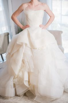 """Vera Wang - Katherine - This beautiful Vera Wang Katherine gown features stunning tiered layers of tulle all throughout the skirt, a sash that ties into a bow in the back, and perfect flower details! This is an incredible unique gown!<br>Wedding Photo Credits: Kyle Goldie with Luma Weddings. <a target=""""_blank"""" href=""""http://lumaweddings.com/"""">http://lumaweddings.com/</a>"""