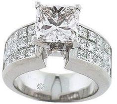 Invisibly Set Diamonds Enhance Center Stone: Prong set princesss cut center diamond with invisible set princess cut diamonds on sides