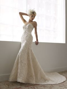 Re-embroidered lace is artfully placed over European net on this mermaid gown. Lace is accented with Swarovski crystals and rhinestones. Strapless neckline finished with zipper closure.