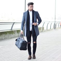 Opt for a grey overcoat and black distressed skinny jeans for your nine-to-five. Turn your sartorial beast mode on and choose a pair of dark brown suede chelsea boots. Shop this look on Lookastic: https://lookastic.com/men/looks/overcoat-long-sleeve-shirt-skinny-jeans/18346 — White Long Sleeve Shirt — Black Scarf — Grey Overcoat — Black Ripped Skinny Jeans — Black Leather Holdall — Dark Brown Suede Chelsea Boots