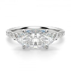 A trendy take on timeless. The East-West Accented Marquise sets a traditionally vertical Contemporary Nexus Diamond™ on its side. It is a study in duality. Classic, yet modern. Strong, yet feminine. Simple, yet luxurious. Like a modern woman, it defies a single category. And the look? Sumptuous in its detail, from the accented band to the intertwined double-claw prongs. It is a ring that commands a second, then a third, look.  Center stone pictured: 2.11 carat Marquise cut, 2.44 total carat…