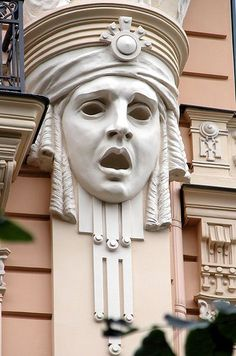 Stunning Art Deco face architectural ornament on pink building in Germany.