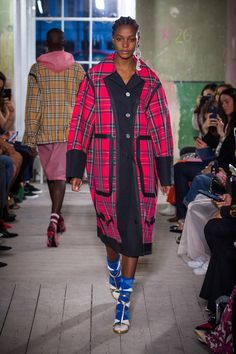 A vibrant red tartan and black car coat cut in an oversized fit with turnback cuffs. Paired with blue argyle knitted socks and gold leather high-heel sandals.