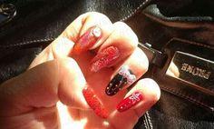 Uñas en diferentes tonos de rojo con accent nail con moño.