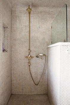 Exposed gold pipes in shower with tiled walls