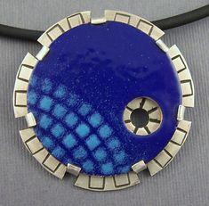 Completely enameled by me! The top layer is light blues squares enameled over a rich blue on a copper circle. I have set the copper layer on a handstamped handcut circle of sterling silver. The pendant is a 1 3/4 cicle with a hidden sterling silver bale. This pendant is signed Lisas