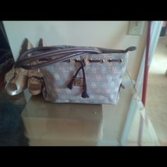 Authentic Monogram Canvas Dooney Bourke bag /Grey Tassel  Canvas tote grey /pink leather handles gently used has three inside pockets zipper closure and leather accents length 12inch height 7.5 depth 4 inch conditions Dooney & Bourke Bags
