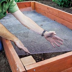 Install Lining in a raised bed - Rake the existing soil at the bottom of the bed to level it, then tamp it smooth. Line the bed with hardware cloth to keep out gophers and moles; trim the cloth with shears to fit around corner posts.