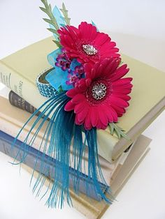 For a fun, funky twist on the traditional corsage, mix Pantone's raspberry-colored Cabaret with a Cockatoo blue. This corsage features gerbera daisies in Cabaret and a crystal bracelet and peacock feather accent in Cockatoo. Homecoming Flowers, Homecoming Corsage, Prom Flowers, Wedding Flowers, Homecoming Mums, Prom Corsage And Boutonniere, Wrist Corsage, Boutonnieres, Corsages