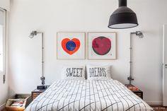 Quarto em estilo urbano tem roupa de cama com estampa preto e branco e quadros em cima da cama.