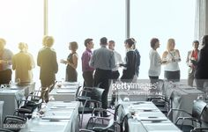 Group of people standing by windows of conference room, socializing during coffee break : Stock Photo