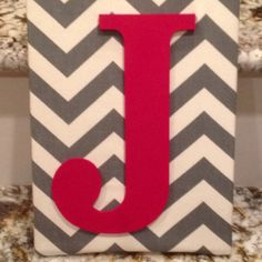 Grey chevron fabric covered canvas with red craft painted cardboard letter adhered with hot glued!