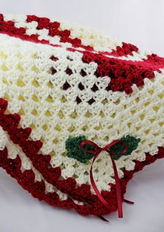 baby christmas blanket. This picture is from an etsy shop. However, it looks to be a large granny square. with holly leaves in the corners sewed on.