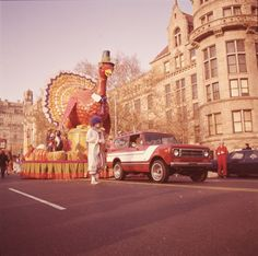 Color photo of a Thanksgiving Day Parade, either Macy's Parade in Manhattan, New York, or Gimbels' Parade in Philadelphia, Pennsylvania. A red and white International Harvester Scout 4x4 is towing a float with a large turkey wearing a white collar and Pilgrim style hat. Bales of straw, pumpkins, and children and adults can be seen on the float. A clown is walking alongside the Scout truck, and in the background is a building with a stone facade. Photo from 1976. Image ID: 98899
