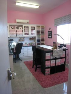 Regular sized craft room. Pink wall and dark furniture. Very pretty crafty storage