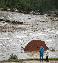 Local residents look over a road washed out by a torrent of water following overnight flash flooding near Left Hand Canyon, south of Lyons, Colo., Thursday, Sept 12, 2013.