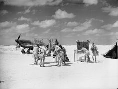 Pilots of No. 274 Squadron don their parachutes and flying clothing from a makeshift rack during a practice scramble at their dispersal at Amriya, Egypt. On the extreme right is Flying Officer Arthur A P Weller and, bareheaded at third left, is the section leader, Flight Lieutenant Peter Wykeham-Barnes. Other pilots include Pilot Officer Philip H Preston and Flight Sergeant J C Hulbert. On the right, and airman chalks up the situation on the operations board.