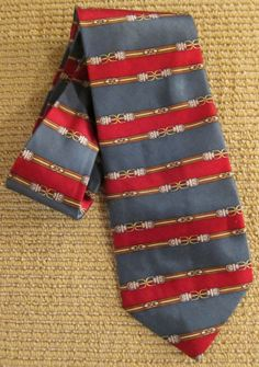 """Classic 80's Belt Buckle Pattern + Striped Silk Tie. Tag Size: One SizeLabel: Bill BlassCirca: 1980'sColor:Multi-ColorFabric: SilkCondition: ExcellentAdditional Information:Nicely designed """"Bill Blass"""" buckled tie...Great colors of festive green and red layered up the tie...Belts line the whole tie...Very COOL tie..."""