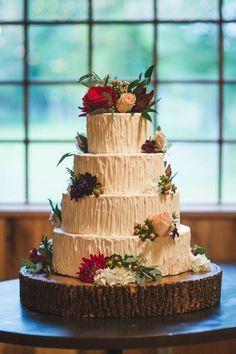 Four-tiered white wedding cake on wood round base | Fete Photography