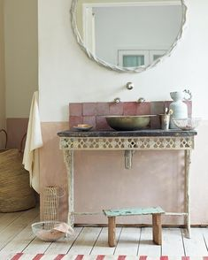 Rough, handmade tiles (from Emery and Cie) and reclaimed ironwork bring a rustic edge to this bathroom, while pastel pink tones (wall in Fired Earth's Afternoon Tea) and wicker accessories keep the look pretty | Styling Ali Brown and Emma Thomas | Photograph by Tom Leighton | Homes & Gardens
