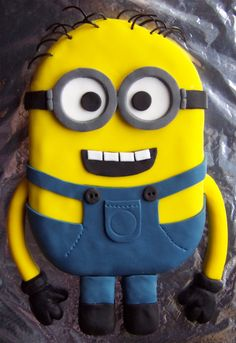Minion cake (Despicable Me), which I did for my son's 10th Birthday. I used liquorice catherine wheels/laces, which I cut up, for the hair. The arms and gloves are solid fondant icing. Later I painted a logo on the pocket with my son's initial 'Z' (instead of the usual 'G') using black food colouring paste and a paintbrush.