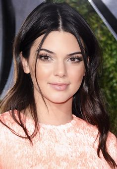 Kendall Jenner wears loose, undone waves, simple makeup, and a nude lip