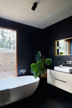 In this modern bathroom, large black tiles have been used on the walls and floor and they contrast the wood frames and white accents like the freestanding bathtub and sink. #BlackBathroom #ModernBathroom #BathroomDesign