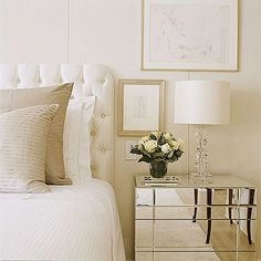 Reflecting Glamour  A crisp white linen-covered headboard, generously tufted with dozens of fabric-covered buttons, lends subtle texture to a streamlined bedroom. Its rounded corners soften the linear geometry of the wall treatment, pinstriped linens, mod Lucite lamp, and mirrored side table.