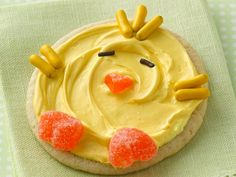 After spreading frosting on cookie, add chocolate chip halves for eyes, yellow candy-coated licorice for feathers and pieces of orange candy slices for beak and feet.