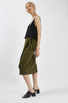 Sitting high on the waist, the full skirt comes with a flattering wrap style silhouette. Finished with a side belt to cinch the waist, pair it with a casual vest and heels for an elegant finish. #Topshop