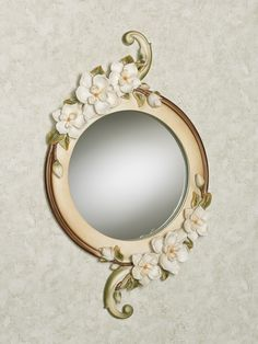 Filled with grace and sweet Magnolia Charm, these elegant blossoms are ones you are sure to admire. Creamy ivory, resin wall mirror has ivory blooms, a scroll design tinted with green, and a central glass mirror.