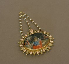 Spanish 17th Century. A Gold mounted polychrome enamel and painted pendant. Decorated with the Holy family and set with fresh water pearls. 90mm drop. 60mm wide.  by The London Auction Rooms