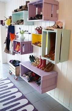 old wooden crates painted bright colors and used for shoe storage near the entry way so that people can take their shoes off right away.