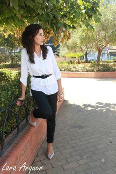 Lara con estilismo de chica trabajadora, resolutiva. Blusa blanca ceñida con cinturón, pantalón de pinza negro y tacones nude.