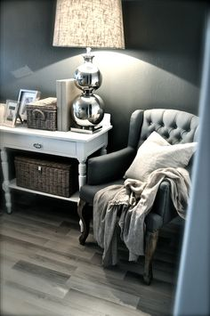 grey wall, white furniture, baskets, and silver lamp